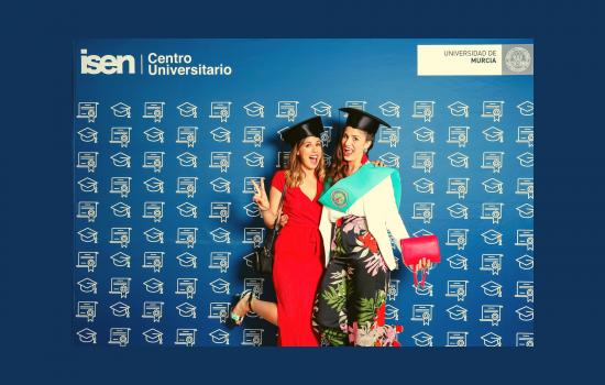 dos alumnas de ISEN celebran la graduación en el photo call.